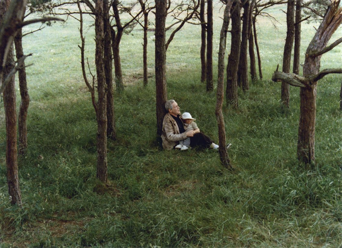 Picture from the film Sacrifice, with a man and a boy sitting on a field, leaning against a tree