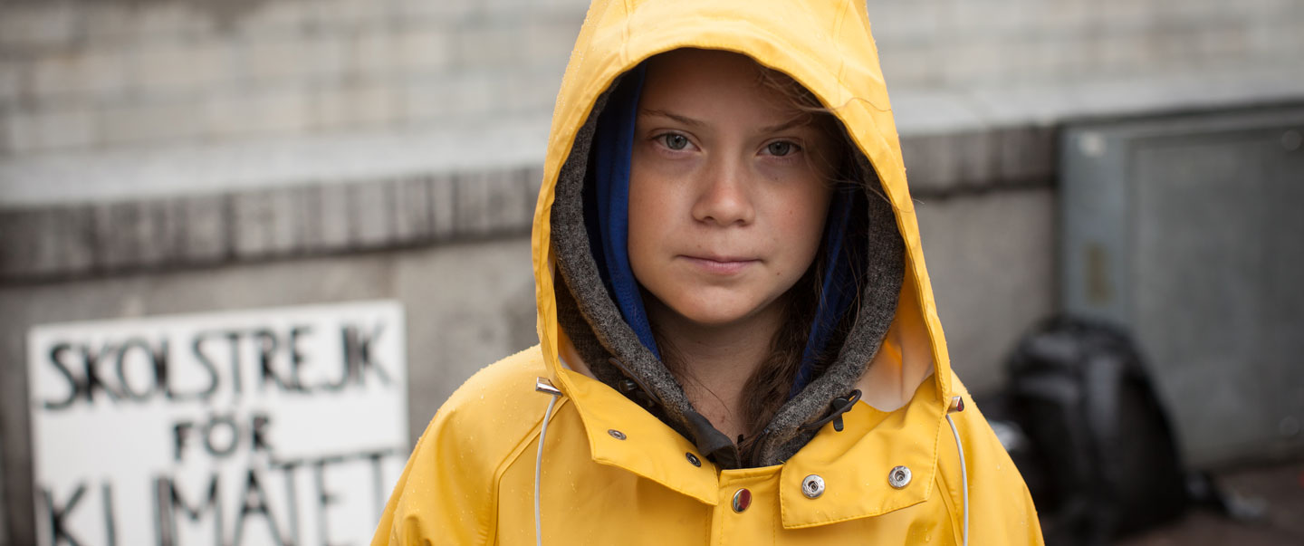 "Greta Thunberg in her yellow raincoat and her sign ""Skolstrejk för klimatet"" in the background"